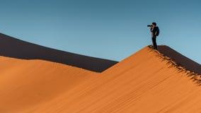 Młoda męska fotograf pozycja na piasek diunie Zdjęcia Royalty Free