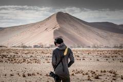 Młoda męska fotograf pozycja przed piasek diuną w pustyni Fotografia Stock