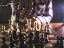Młoda męska grandmaster ręka robi kolejnemu krokowi bawić się szachy w ciemnym miejscu na turnieju obrazy royalty free