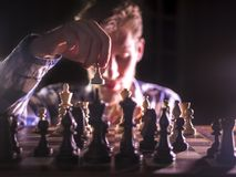 Młoda męska grandmaster ręka robi kolejnemu krokowi bawić się szachy w ciemnym miejscu na turnieju fotografia stock
