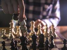 Młoda męska grandmaster ręka robi kolejnemu krokowi bawić się szachy w ciemnym miejscu na turnieju zdjęcia royalty free