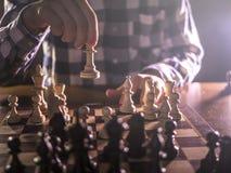 Młoda męska grandmaster ręka robi kolejnemu krokowi bawić się szachy w ciemnym miejscu na turnieju zdjęcia stock