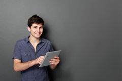 Młoda męska ono uśmiecha się używa cyfrowa pastylka Zdjęcie Royalty Free