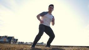 Młoda męska parkour tricker bluza wykonuje zadziwiać trzepnięcia przed słońcem zdjęcie wideo