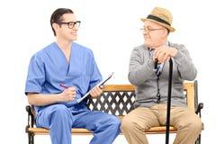 Młoda męska pielęgniarka opowiada starszy dżentelmen sadzający na ławce Fotografia Royalty Free