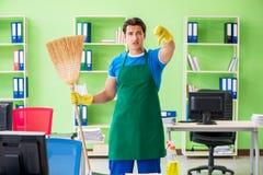 Młoda męska przystojna fachowa cleaner cleaning podłoga z miotłą obraz royalty free