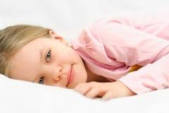 Młoda mała dziewczynka kłaść na łóżku z pokojowym twarzy wyrażeniem Fotografia Stock