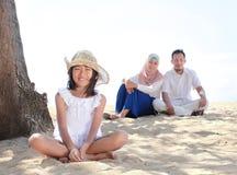 Młoda mała dziewczynka ono uśmiecha się z jej rodzicem jako backgr w plaży Fotografia Royalty Free