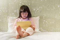 Młoda mała dziewczynka w pyjamas bawić się pastylkę na łóżku obrazy royalty free