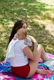 Młoda mama dba jej dziecka w czkać pozycję na trawie i być usytuowanym, sceny matka i niemowlaka przy colourful koc, outside obraz stock