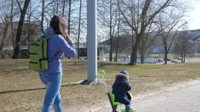 Młoda matka i chłopiec chodzimy outside Dzieciak jeździć na łyżwach obsiadanie na hulajnoga zbiory