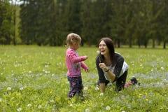 Młoda matka z córką bawić się na zielonej łące troszkę zdjęcie royalty free