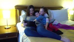 Młoda matka z dwa dziećmi kłama w hotelu w łóżku Używa internet przez pastylka komputerów Są szczęśliwi zdjęcie wideo