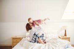 Młoda matka z małą córką siedzi indoors na łóżku w ranku, bawić się fotografia royalty free