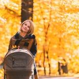 Młoda matka z spacerowiczem chodzi przez jesień parka fotografia stock