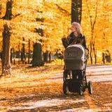 Młoda matka z spacerowiczem chodzi przez jesień parka obrazy royalty free
