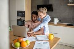 Młoda międzyrasowa para używa laptop wpólnie ma śniadanie w domu zdjęcia stock