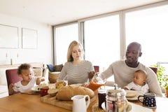 Młoda międzyrasowa rodzina z małymi dziećmi ma śniadanie Zdjęcia Stock