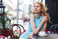 Młoda miedzianowłosa dziewczyna przy stołem w kawiarni obrazy stock