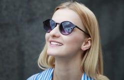 Młoda miedzianowłosa dziewczyna w okularach przeciwsłonecznych z ciemnymi szkłami w ramie, dzień, plenerowy obraz royalty free