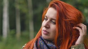 Młoda miedzianowłosa kobieta oddycha czyste powietrze, chodzi w ranku w jesień lasu zwolnionym tempie zbiory