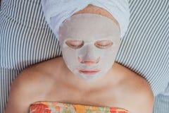 Młoda miedzianowłosa kobieta relaksuje na łóżku Szkotowa maska na jej twarzy Zdjęcia Stock