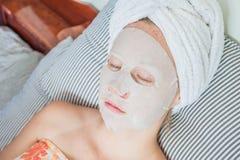 Młoda miedzianowłosa kobieta relaksuje na łóżku Szkotowa maska na jej twarzy Zdjęcie Stock
