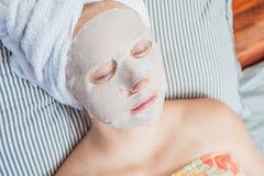 Młoda miedzianowłosa kobieta relaksuje na łóżku Szkotowa maska na jej twarzy Obraz Stock