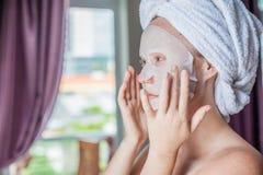 Młoda miedzianowłosa kobieta robi twarzowemu maski prześcieradłu Obrazy Stock