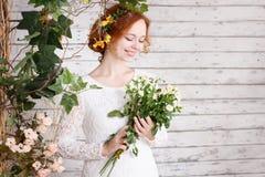 Młoda miedzianowłosa panna młoda w prostej koronki sukni Fotografia Stock