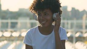 Młoda millennial kobieta słucha muzyka i taniec na ulicie z słuchawki zdjęcie wideo