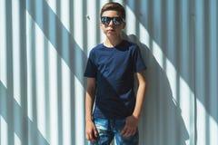 Młoda modniś chłopiec w okularach przeciwsłonecznych ubierających w czarnej koszulce jest stojakami salowymi przeciw biel ścianie Obraz Stock