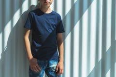 Młoda modniś chłopiec w okularach przeciwsłonecznych ubierających w czarnej koszulce jest stojakami salowymi przeciw biel ścianie Fotografia Stock