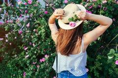 Młoda modniś dziewczyna jest ubranym kapeluszowego odprowadzenie kwitnienie różami Kobieta cieszy się kwiaty w parku Lato strój obrazy stock