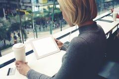 Młoda modniś dziewczyna rezerwuje hotel przez przenośnej cyfrowej pastylki z kopii przestrzenią na ekranie zdjęcie royalty free