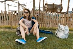 Młoda modniś dziewczyna w kapeluszu z szkłami siedzi odpoczywać na trawie w parku odtwarzanie i rozrywka fotografia royalty free