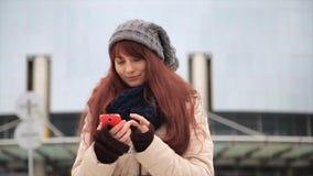 Młoda modniś dziewczyna z smartphone na uliczny ono uśmiecha się przy kamerą zdjęcie wideo