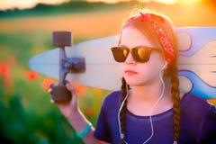 Młoda modniś dziewczyna z warkoczami w okularach przeciwsłonecznych i czerwona szarfa na h Obraz Royalty Free