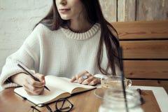 Młoda modniś dziewczyny praca w kawiarni, z nutowym ochraniaczem w cukiernianym pobliskim nadokiennym lunchu czasie z kawą Obrazy Stock