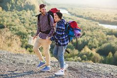 Młoda modniś para wycieczkuje w górach podczas długiej wycieczki z plecakami Szczęśliwi caucasian podróżnicy zadziwiać zdjęcie stock