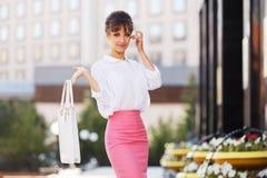 Młoda mody biznesowa kobieta w białej koszula i menchia ołówek omijamy zdjęcia stock