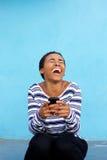 Młoda murzynka śmia się z telefonem komórkowym przeciw błękit ścianie Fotografia Stock