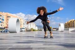 Młoda murzynka na rolkowych łyżwach jedzie outdoors na miastowej ulicie z otwartymi rękami Uśmiechnięta dziewczyna z afro fryzurą obrazy royalty free