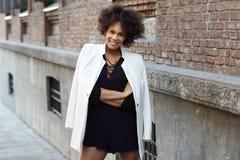 Młoda murzynka ono uśmiecha się w miastowym backgroun z afro fryzurą Zdjęcia Stock