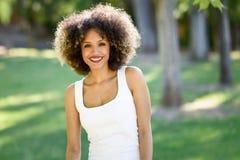 Młoda murzynka ono uśmiecha się w miastowym parku z afro fryzurą zdjęcia royalty free
