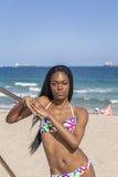 Młoda murzynka przy plażą, jest ubranym bikini Opierać na poręczu Zdjęcie Stock