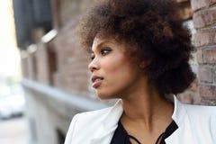 Młoda murzynka z afro fryzury pozycją w miastowym backgrou Zdjęcie Stock