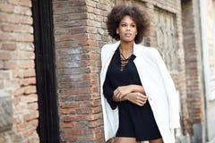 Młoda murzynka z afro fryzury pozycją w miastowym tle fotografia stock