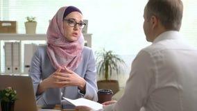 Młoda muzułmańska biznesowa kobieta trząść ręki z caucasian mężczyzną podczas spotkania w biurze zbiory