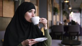 Młoda muzułmańska kobieta jest ubranym czarnego hijab obsiadanie w nowożytnej kawiarni Pić kawę od białego zamyślenia i filiżanki zbiory